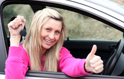 Jolly female driver showing a key Royalty Free Stock Images