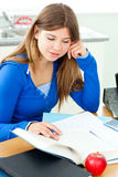 Jolly female teenager studying in the kitchen Stock Images