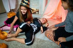Jolly girl tickling foot of friend. Playful cute little witch tickling foot of boy dressed as skeleton lying on floor, smiling friend observing them at Halloween Stock Photo