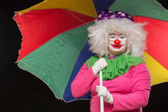 Jolly good funny clown with a multi-colored umbrella on a black Royalty Free Stock Photos