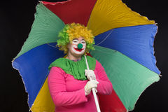 Jolly good funny clown with a multi-colored umbrella on a black Stock Photography