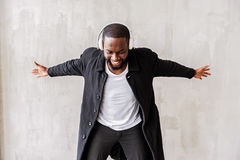 Jolly handsome african man with beard enjoying his beloved songs via earphones. Falling to fun. Happy trendy young guy is stretching his arms to sides as if Stock Image