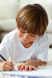 Jolly little boy drawing lying on the floor Royalty Free Stock Image