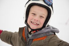 Jolly little child portrait in winter coat and protection sport helmet outdoor at winter time. stock images