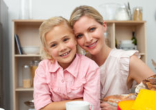 Jolly little girl eating fruit with her mother Royalty Free Stock Photo