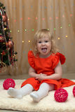Jolly little girl showing tonque near the christmas tree Stock Images