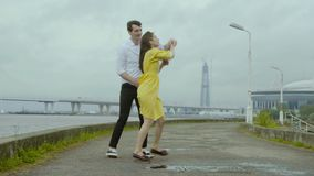 Merry girl and happy boy dance emotionally polka on rain pools of a pier stock video