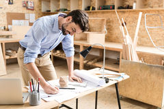 Jolly lumber craftsman making drafts of product in workshop Stock Images