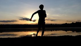 Jolly man dances rave on a lake bank at sunset in slo-mo