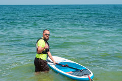 Jolly man with a paddle floats on stand up paddle board. Young bearded man with an oar preparing floats on a paddle board in the sea, it shows thumb Stock Photo
