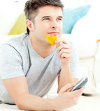 Jolly man with remote eating crisps on the floor Stock Image