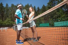 Jolly man and woman are playing tennis against each other royalty free stock images