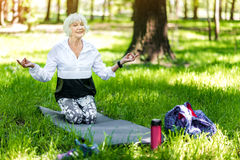Jolly old lady making relaxation exercises in forest Royalty Free Stock Images