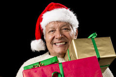 Jolly Old Man With Santa Cap And Three Xmas Gifts. Hilarious aged gentleman carrying three Christmas gifts loaded onto his chest. Presents wrapped in plain red Royalty Free Stock Photo
