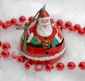 Jolly Old St. Nick Decoration. A bright and shiny Christmas tree decoration in the snow stock images