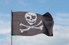 Jolly Roger. Flag against blue sky Royalty Free Stock Photography