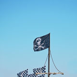 Jolly Roger in a blue sky. The Jolly Roger flag traditionally flown by English sea pirates when about to attack merchant shipping Royalty Free Stock Photos