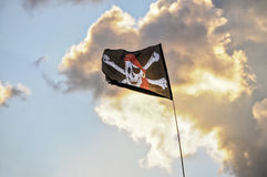 Jolly Roger flag. Jolly Roger pirate flag with a skull and crossbones on a background of clouds Stock Photography