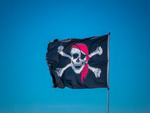 The jolly roger flag. The pirates flag, the jolly roger, waving on a blue sky background Stock Images