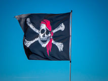 The jolly roger flag. The pirates flag, the jolly roger, waving on a blue sky background Royalty Free Stock Photography