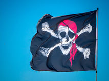 The jolly roger flag. The pirates flag, the jolly roger, waving on a blue sky background Stock Image