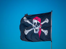 The jolly roger flag. The pirates flag, the jolly roger, waving on a blue sky background Stock Photography