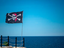The jolly roger flag. The pirates flag, the jolly roger, waving on a blue sky and a blue sea background Stock Photo
