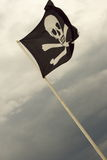 Jolly Roger pirate flag. A Jolly Roger Pirate flag in black and white with skull in crossbones flies high in the sky Royalty Free Stock Photos