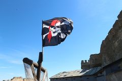 Jolly roger pirate flag in the blue sky Stock Images