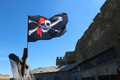 Jolly roger pirate flag in the blue sky Royalty Free Stock Photos