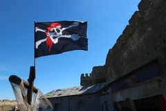 Jolly roger pirate flag in the blue sky Royalty Free Stock Images