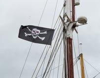 Jolly Roger/piratkopierar flaggaskallen och korslagda benknotor som flyger från masten av ett segla skepp arkivfoto