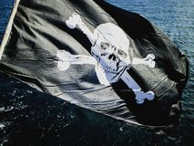 Jolly Rogers pirate flag flying from a sailing boat royalty free stock image