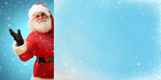 Jolly Santa Claus holding banner with blue space for Your Text. Merry Christmas & New Year's Eve concept. Close up on blurred blue background Stock Photography