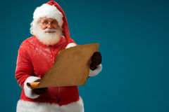 Jolly Santa Claus holding vintage paper blank sign. Stock Image