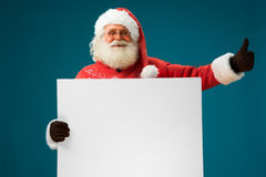 Jolly Santa Claus holding white blank banner for copy space  of your text. Stock Photo