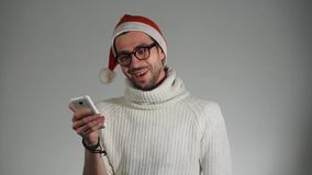 Jolly Santa Claus receives SMS, surprised the news and calling on the phone stock video footage