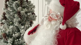 Jolly Santa Claus sitting by the Christmas tree and talking on the phone stock video