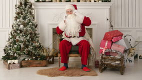 Jolly Santa Claus sitting by the Christmas tree and talking on the phone stock footage