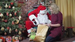 Jolly Santa looks in the bag with gifts surprised girl. Jolly Santa looks in the bag with gifts beautiful woman surprised stock footage