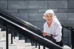 Jolly senior woman raising up huge stone ladder outside. Waist up portrait of happy old lady going upstairs outdoor. She is stopping for a while to rest and stock image