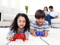 Jolly siblings playing video games. Lying on the floor with their parents in the background Stock Photos