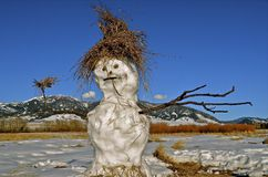 Jolly Snowman below the Mountains. Below a mountain range a jolly snowman with a weed and grass hat extends arms Royalty Free Stock Photography