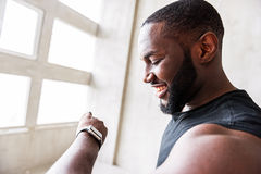Jolly sportsman looking cheerfully at timer on his sport watch. Good result. Happy african bearded athlete is smiling while checking time on his wristwatch. Copy Royalty Free Stock Photos
