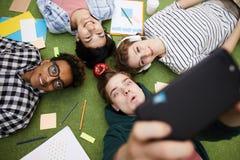 Jolly student friends taking selfie on floor royalty free stock image