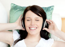 Jolly teen girl listening music lying on a sofa Stock Image