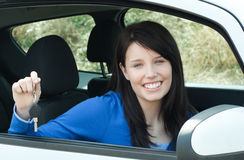 Jolly teen girl sitting in her car holding keys. After bying a new car Stock Photo