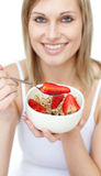 Jolly woman eating cereals with strawberries Royalty Free Stock Photo