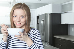 Jolly woman having breakfast at home Stock Photos