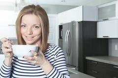 Jolly woman having breakfast at home Stock Photos